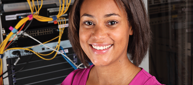 a girl stands in front of a networking computer