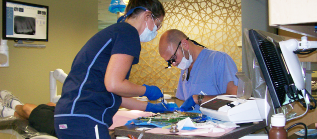students work with dental tools on a patient