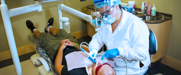 a dental hygienist cleans a man's teeth