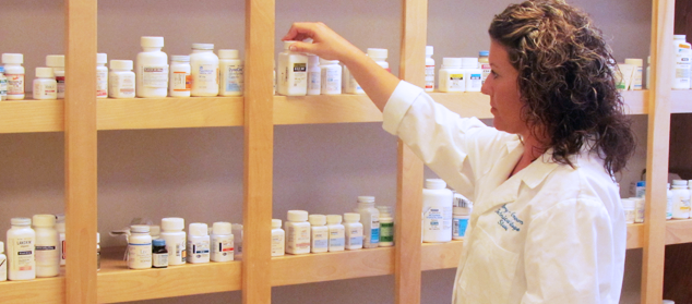 a pharmacy tech reviews a shelf of medication