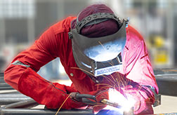 a welder works while covered with protective gear